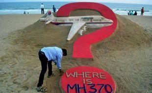 """""""Où est le MH370?"""", oeuvre de l'artiste indien Sudarsan Pattnaik (à gauche, au premier plan), sur une plage de Puri, en Inde, le 7 mars 2015"""