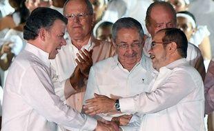 Le président colombien Juan Manuel Santos (à g.) et le chef des Farc Timochenko (à dr.) après la signature de l'accord, en présence du président cubain Raul Castro, à Carthagène, le 26 septembre 2016.