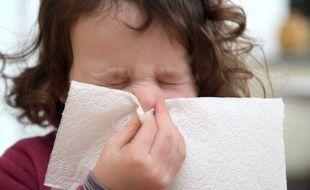 Petite fille enrhumée se mouchant.