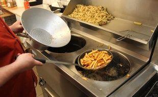 Des frites prêtes à sortir de l'huile bouillante (illustration).