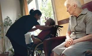 Des personnes âgées prises en charge par une aide à domicile, sont assises dans la salle commune d'un domicile collectif (Illustration)