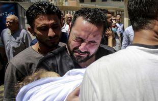 Les gens assistent aux funérailles de victimes d'une frappe aérienne dans la ville de Gaza, le 16 mai 2021.