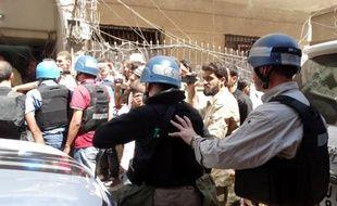 Photo fournie par Shaam News Network montrant les experts de l'ONU entourés par des combattants rebelles, des civils et des journalistes le 28 août 2013 à leur arrivée à Ghouta, l'un des sites de l'attaque chimique présumée