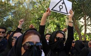 Des iraniennes, le visage caché pour ne pas être reconnues, crient des slogans lors d'une manifestation à Ispahan afin de demander des mesures de sécurité supplémentaires après des attaques à l'acide perpétrées contre des femmes, le 22 octobre 2014