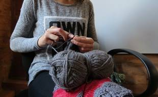 Une jeune femme en train de tricoter (illustration).