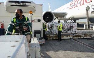 Un employé décharge des cartons de vaccins Oxford / AstraZeneca Covid-19, livrés dans le cadre de l'initiative Covax dirigée par l'ONU