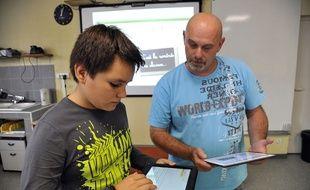 Un collégien apprend à se servir d'une tablette (photo d'illustration)