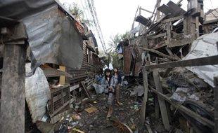 Une femme marche dans les décombres de maisons touchées par une explosion, le 29 décembre 2011, à Rangoun (Birmanie).