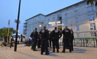 Des policiers montent la garde devant le commissariat de Trappes le 21 juillet 2013, après des affrontements entre la police et des habitants, suivant le contrôle d'identité de Cassandra Belin