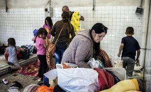 Des migrants des pays de l'Est s'installent temporairement dans un local à Décines-Charpieu après avoir séjourné dans des bâtiments de l'armée et du diocèse de Lyon, le 21 avril 2015