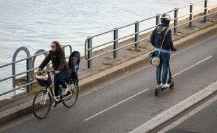 Une cycliste et un homme à trottinette circulent sur la piste cyclable de la voie Georges-Pompidou, à Paris (15e).
