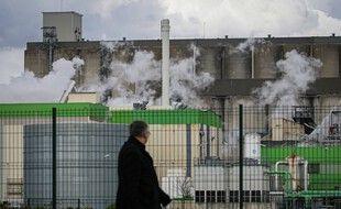 Un passant regarde la fumée s'élever d'un bâtiment de la société SAIPOL (groupe Avril) classé SEVESO, touché par un incendie, à Grand-Couronne, près de Rouen, dans le nord de la France, le 13 mars 2020.