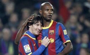 Le défenseur français du FC Barcelone, Eric Abidal, dans les bras de Lionel Messi lors d'un match de Liga contre l'Atlético Madrid, le 5 février 2011.