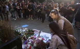 Deux jeunes femmes déposent des fleurs au Albert Square de Manchester en hommage aux victimes de l'attentat-suicide.
