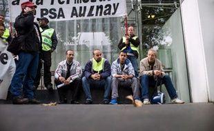 Des manifestants devant le quartier général du groupe automobile PSA Peugeot Citroën, à Paris, le 18 septembre 2013