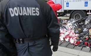 Un gendarme regarde, le 27 janvier 2011 à Paris, des articles de contrefacon avant leurs destructions.