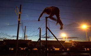 Un migrant franchit une barrière pour accéder au site d'Eurotunnel, à Calais, en août 2015.
