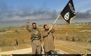 Des militants de l'Etat islamique brandissent le drapeau de l'organisation à Falloudja, en Irak, le 28 juin 2015.