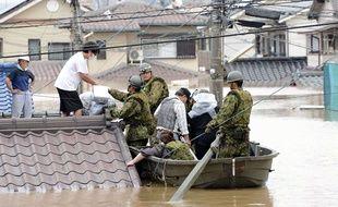 Les forces de défense japonaises aident les habitants de Kurashiki, dans la préfecture de Okayama, à évacuer leurs maisons après les pluies torrentielles qui se sont abattues dans la région le 7 juillet 2018.