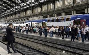 Des passagers attendent un train, dans la gare de Lyon à Paris le 16 juin 2014