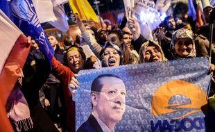 Des partisans du parti turc AKP, au pouvoir, brandissent des drapeaux et un portrait du président turc, Recep Tayyip Erdogan, après la victoire du parti aux législatives anticipées, le 1er novembre 2015, à Istanbul.