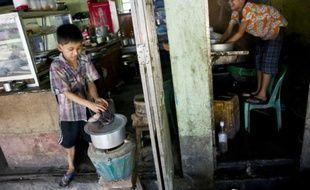 Saw Paing Htway (d) et Min Min, deux enfants qui travaillent dans un teashop (salon de thé) à Rangoun, le 21 octobre 2015