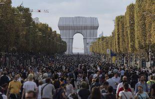 """Des gens marchent le long de l'avenue des Champs Elysées, à Paris, lors de la """"journée sans voitures"""", avec l'Arc de Triomphe en arrière-plan, le 19 septembre 2021."""
