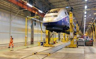 Un salarié de PSA marche le long d'un TGV en suspension au sein de l'usine de La Janais, près de Rennes. Le site a rénové les rames de TGV de 2014 à 2017.
