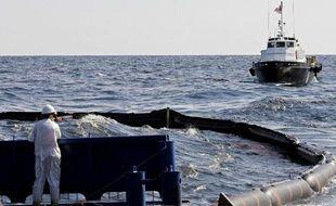 Des ouvriers tentent, le 27 avril 2010, d'endiguer la nappe de pétrole qui s'échappe après l'explosition de la plateforme pétrolière Deepwater dans le golfe du Mexique.