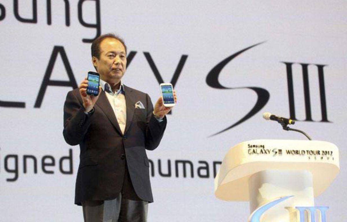 Shin Jong-kyun, le président de la division mobile de Samsung, pose avec le nouveau smartphone du groupe, le Galaxy S3.  – AP/SIPA