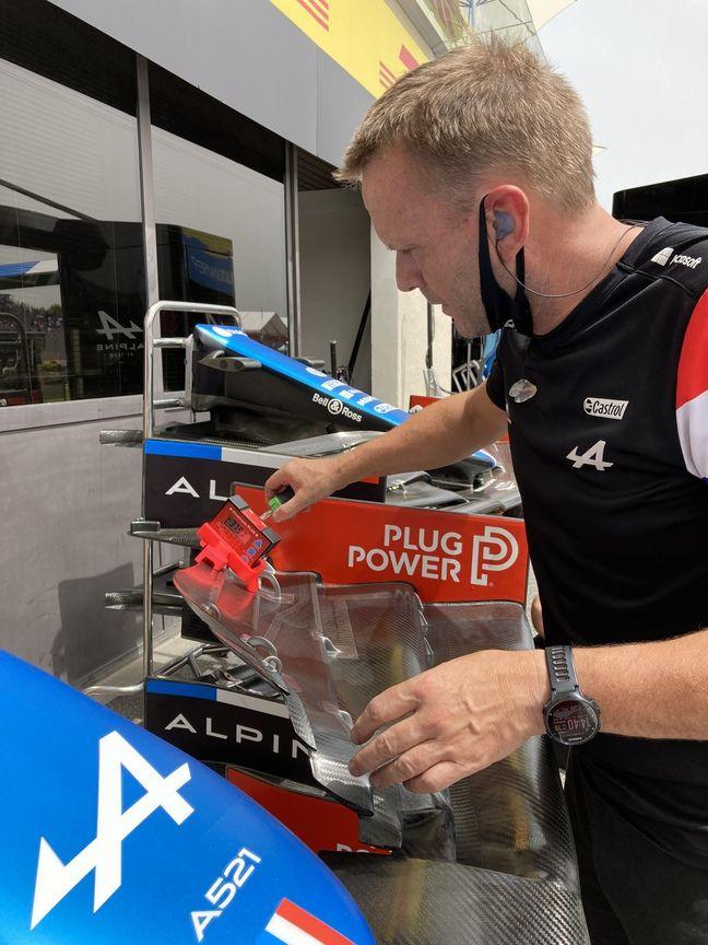 Un mécanicien de chez Alpine en train de controler le degrés d'inclinaison de l'aileron avant.