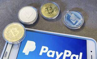 Le logo PayPal sur un smartphone et des pièces illustrant de la monnaie virtuelle.
