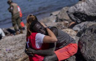 Un migrant est réconforté par un membre de la Croix-Rouge espagnole près de la frontière entre le Maroc et l'Espagne, dans l'enclave espagnole de Ceuta, le 18 mai 2021.