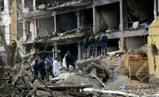Des policiers turcs devant un bâtiment détruit par l'explosion d'une voiture piégée contre un commissariat, le 14 janvier 2016 à Cinar, dans le sud-est