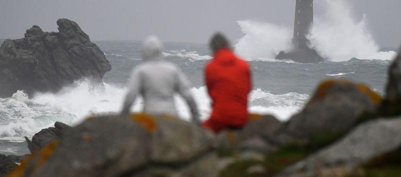 """Les passants observent les vagues déferlant sur le """"Phare du Four"""" au large de la ville occidentale de Porspoder le 2 novembre 2019, quelques heures avant la tempête Amélie."""