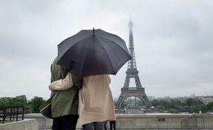Un couple sous un parapluie observe la Tour Eiffel.