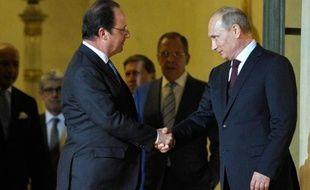 Poignée de mains entre le président russe Vladimir Poutine (d) et François Hollande à l'Elysée le 5 juin 2014
