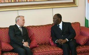 Le président ivoirien Alassane Ouattara(d) parle avec le ministre français des Affaires étrangères Jean-Marc Ayrault à Abidjan le 15 mars 2016