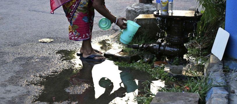 Une jeune femme collecte de l'eau à un point de distribution dans un bidonville de Bombay, en Inde, en mars 2017.