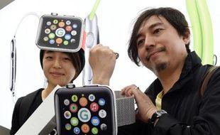 Makoto Saito (g) et Kazumi Oda (d) posent après avoir acheté une montre Apple Watch à Tokyo le 24 avril 2015
