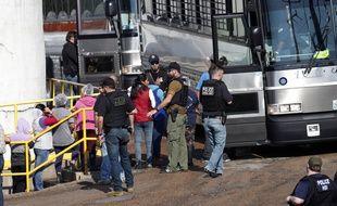Des travailleuses menottées sont escortées vers un bus qui les emmènera dans des centres de détention. Usine Koch Foods, Morton, le 7 août 2019