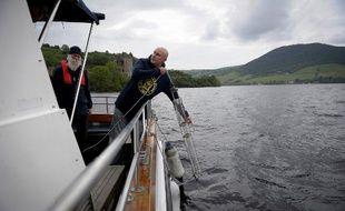Le professeur Neil Gemmel prélève des échantillons d'eau du lac le 11 juin 2018, sous le regard attentif naturaliste Alain Shine, le responsable du Loch Ness Project» qui continue l'enquête.