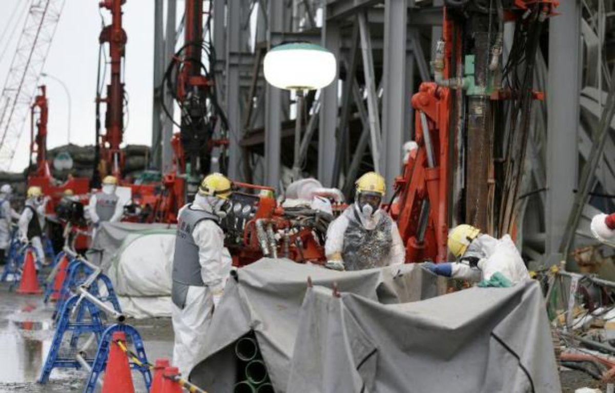 Des techniciens travaillent à la centrale accidentée de Fukushima Daiichi, le 9 juillet 2014, à Okuma – Kimimasa Mayama Pool