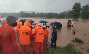 Des membres de la National Disaster Response Force viennent en aide à des personnes prises par les eaux après un glissement de terrain à Chiplun, dans l'ouest de l'Inde, le 23 juillet 2021.