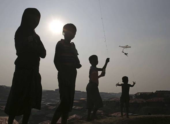 "Rohingya Muslim children are silhouetted against the setting sun as they fly kites in Kutupalong refugee camp on Thursday, Nov. 23, 2017, in Bangladesh. Since late August, more than 620,000 Rohingya have fled Myanmar's Rakhine state into neighboring Bangladesh, seeking safety from what the military described as ""clearance operations."" The United Nations and others have said the military's actions appeared to be a campaign of ""ethnic cleansing,"" using acts of violence and intimidation and burning down homes to force the Rohingya to leave their communities."