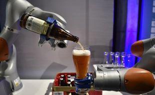 Deux bras robotiques du fabricant de robots industriels Kuka versent une bière à Berlin le 2 mai 2017 (Illustration)
