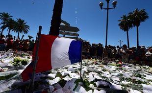 Un drapeau français entouré de bouquets de fleurs et autres hommages aux victimes de la tuerie de Nice perpétrée jeudi 14 juillet sur la promenade des Anglais.