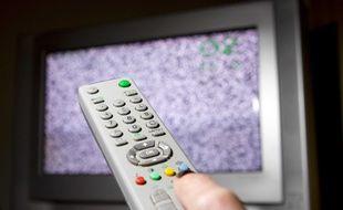 Un télécommande devant un écran de télévision qui grésille.
