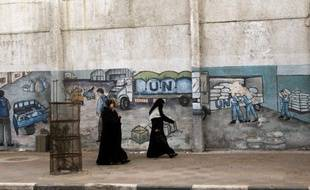 Palestinian women walk in front of graffiti next to the UN headquarters building in Gaza City on April 5, 2013. Gaza's Hamas rulers urged the United Nations to reconsider its suspension of food aid for Palestinian refugees, imposed after protesters stormed a UN depot. AFP PHOTO/MOHAMMED ABED