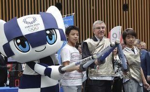 Le président du CIO Thomas Bach pose avec la mascotte des JO de Tokyo le 24 juillet 2019, un an avant le début des Jeux.